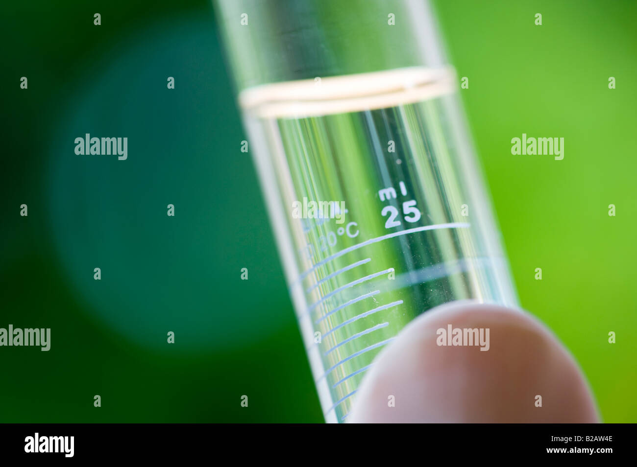 hand holding small test tube of clear liquid outdoors - Stock Image