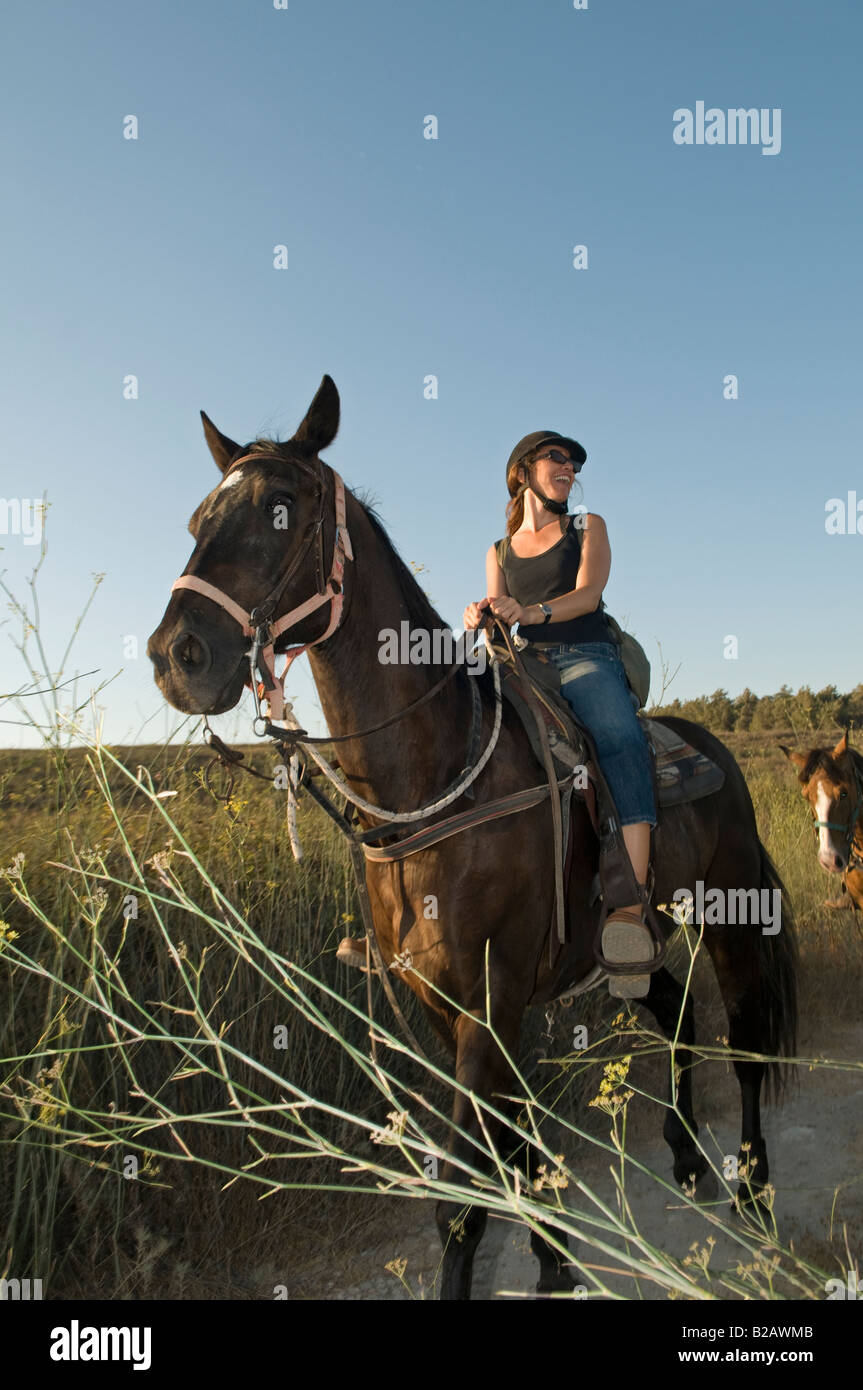 An Israeli woman riding a horse in the Menashe Heights or Ramot Menashe located on the Carmel Range northern Israel - Stock Image