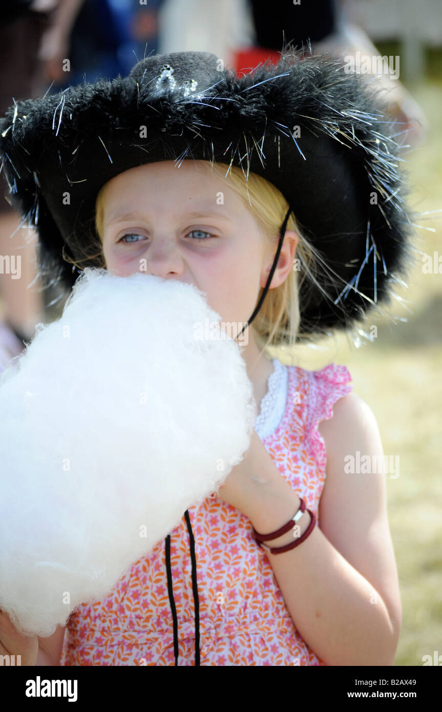 Royalty free photograph of a little girl eating candy floss at a music festival with cowboy costume in summer sunshine - Stock Image
