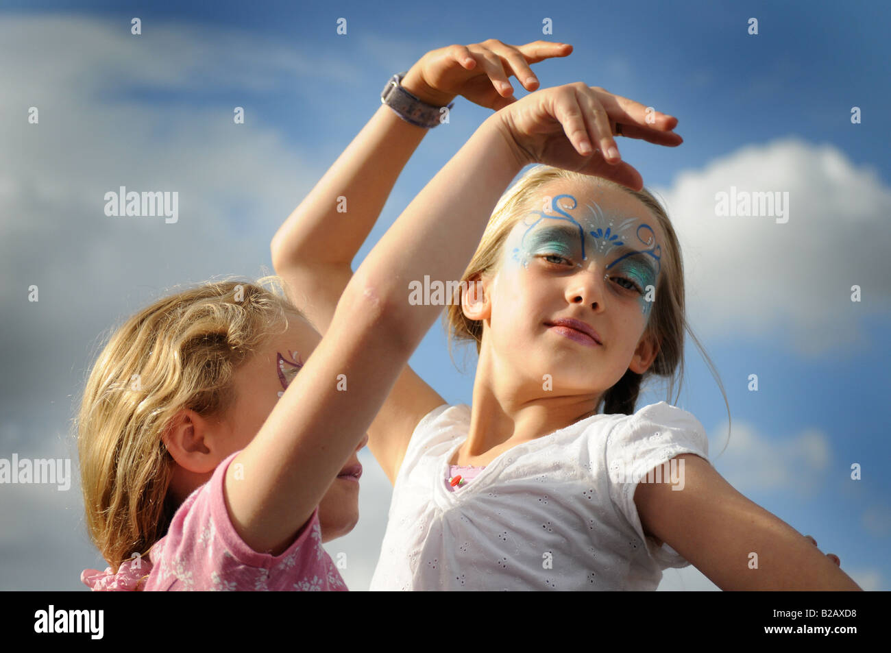 Photograph of two young girls with painted faces dancing at a music festival in the UK - Stock Image