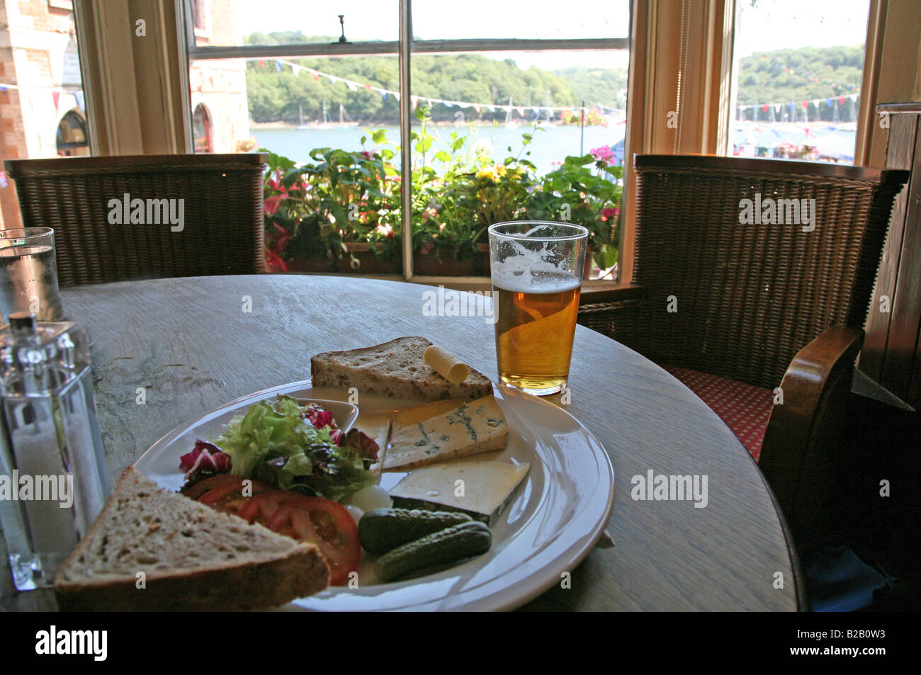 A traditional English ploughman's lunch and a pint of beer in The King of Prussia pub at the sea front at Fowey, - Stock Image