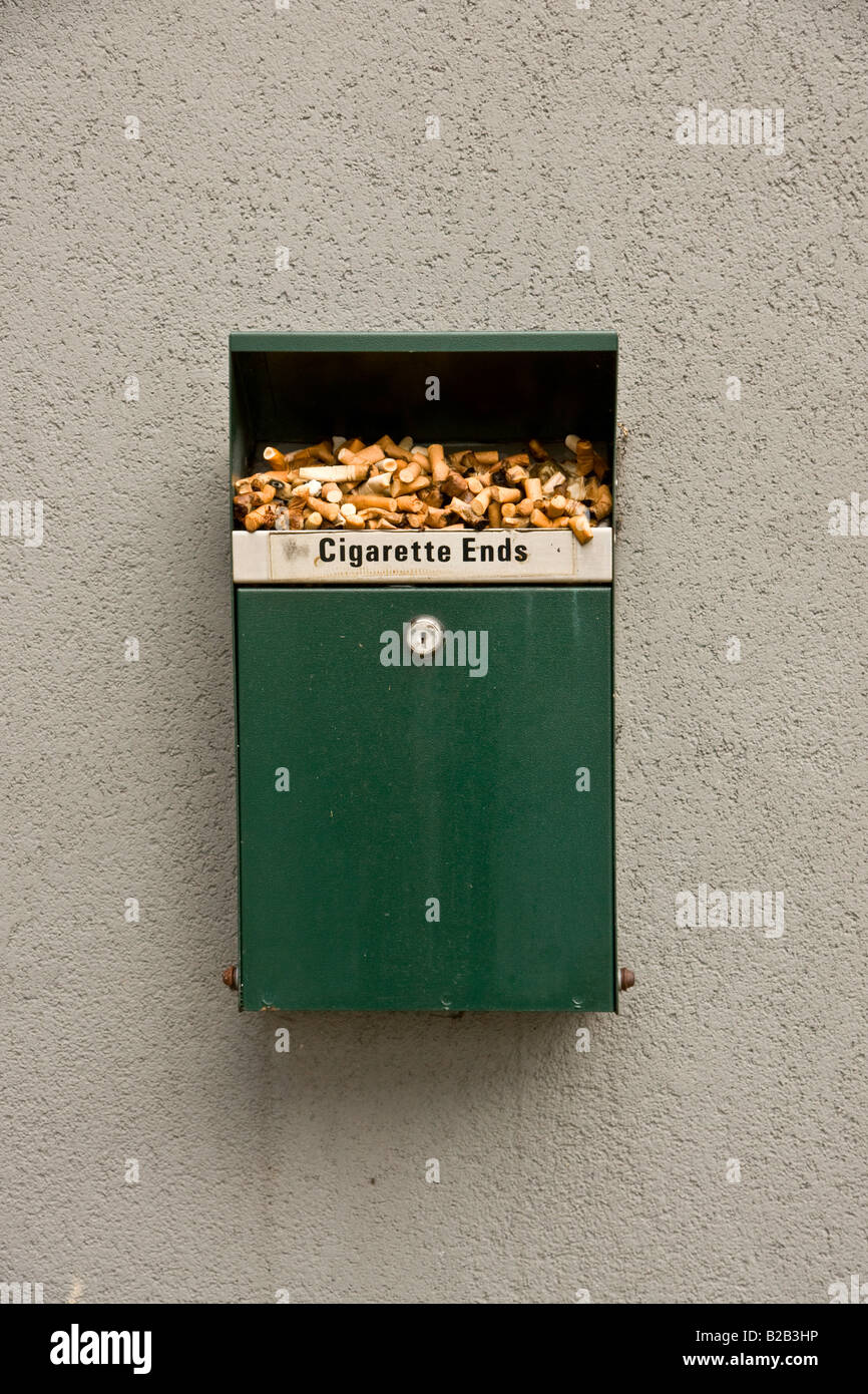 Cigarette ends overflowing an ash tray on the wall of an office block. - Stock Image