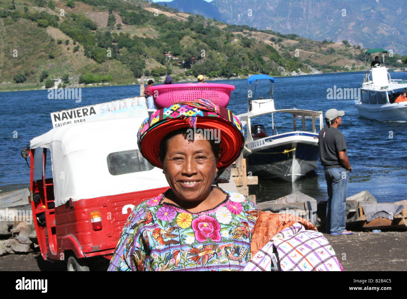 A local woman with a basket on her head selling fabrics on the shores of Atitlan in Santiago in the highlands of - Stock Image