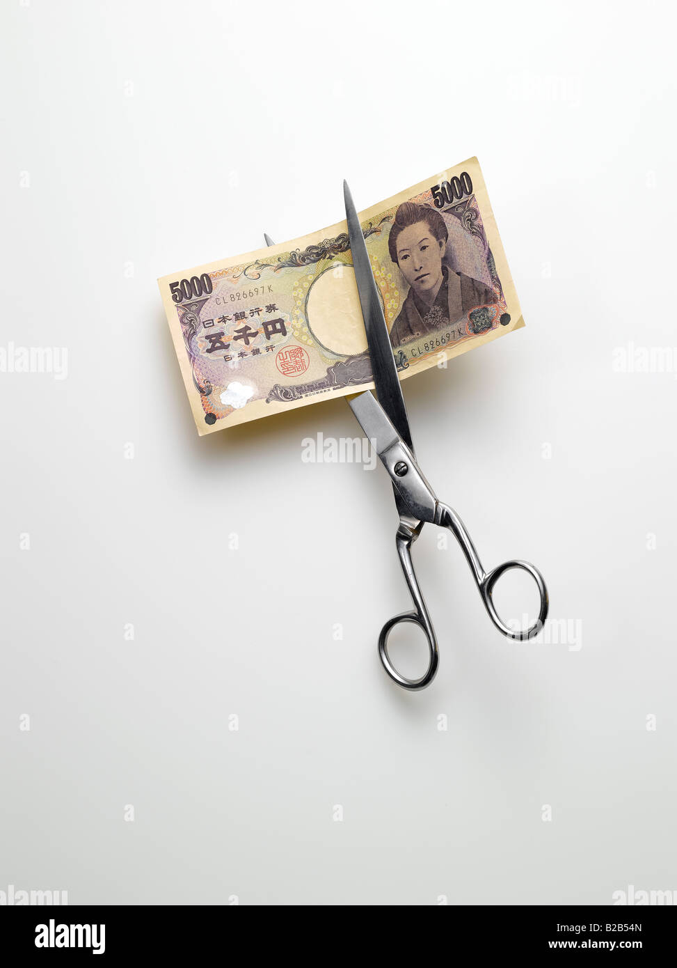 scissors cutting Japanese yen money on white background - Stock Image