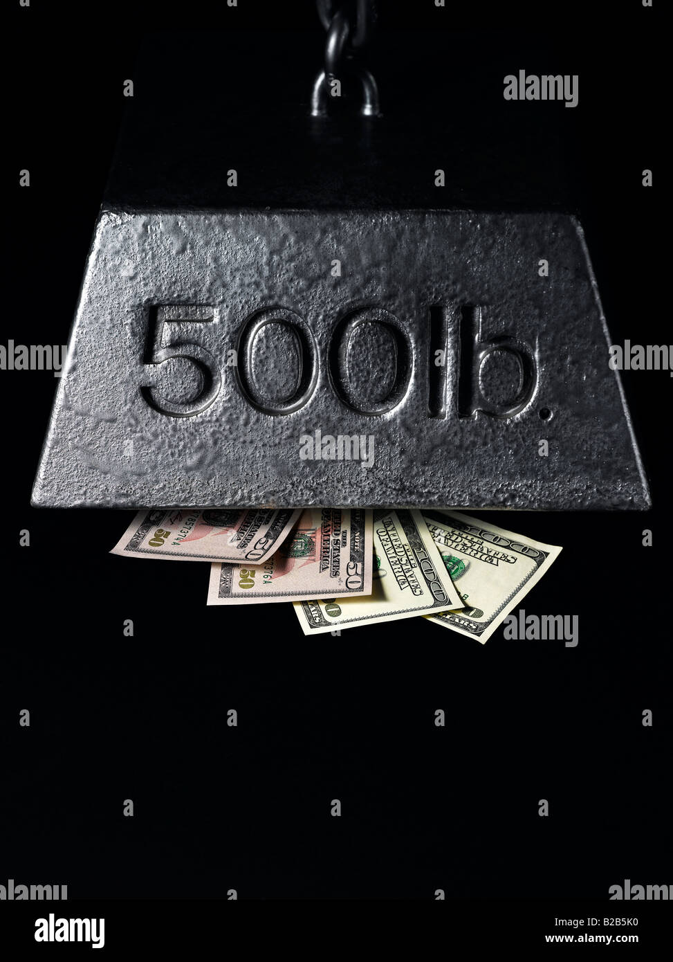 money pressured and squeezed under financial weight Stock Photo