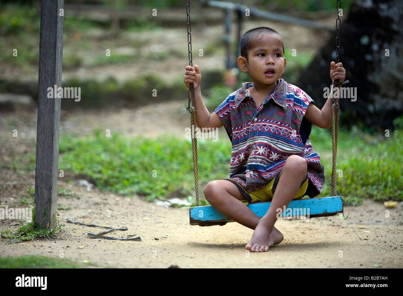 A Mangyan child plays on a swing in Panaytayan community near Mansalay, Oriental Mindoro, Philippines - Stock Image