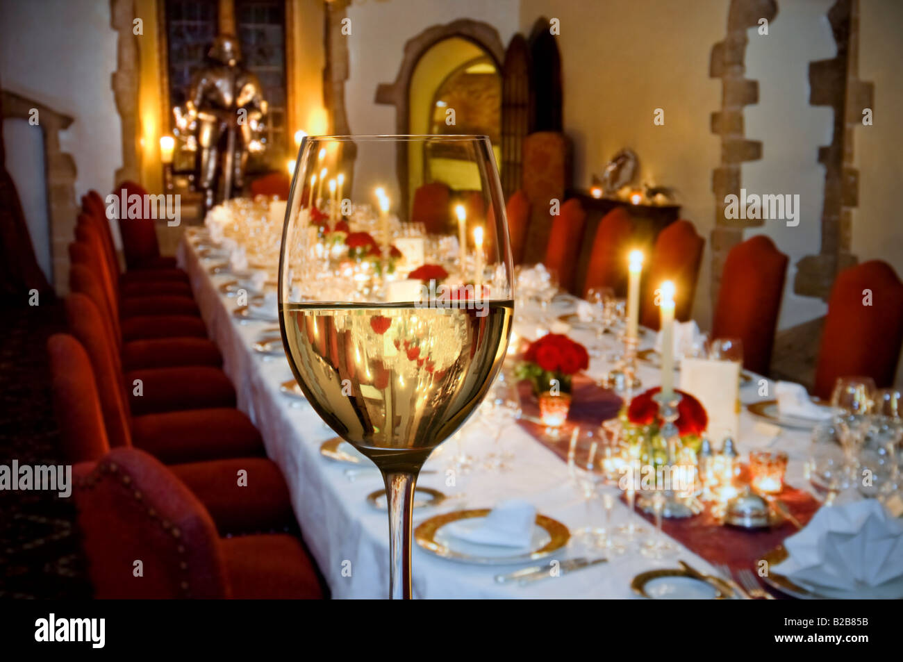 glass of fine white wine in foreground with a formal seated candlelit dinner party table prepared in background