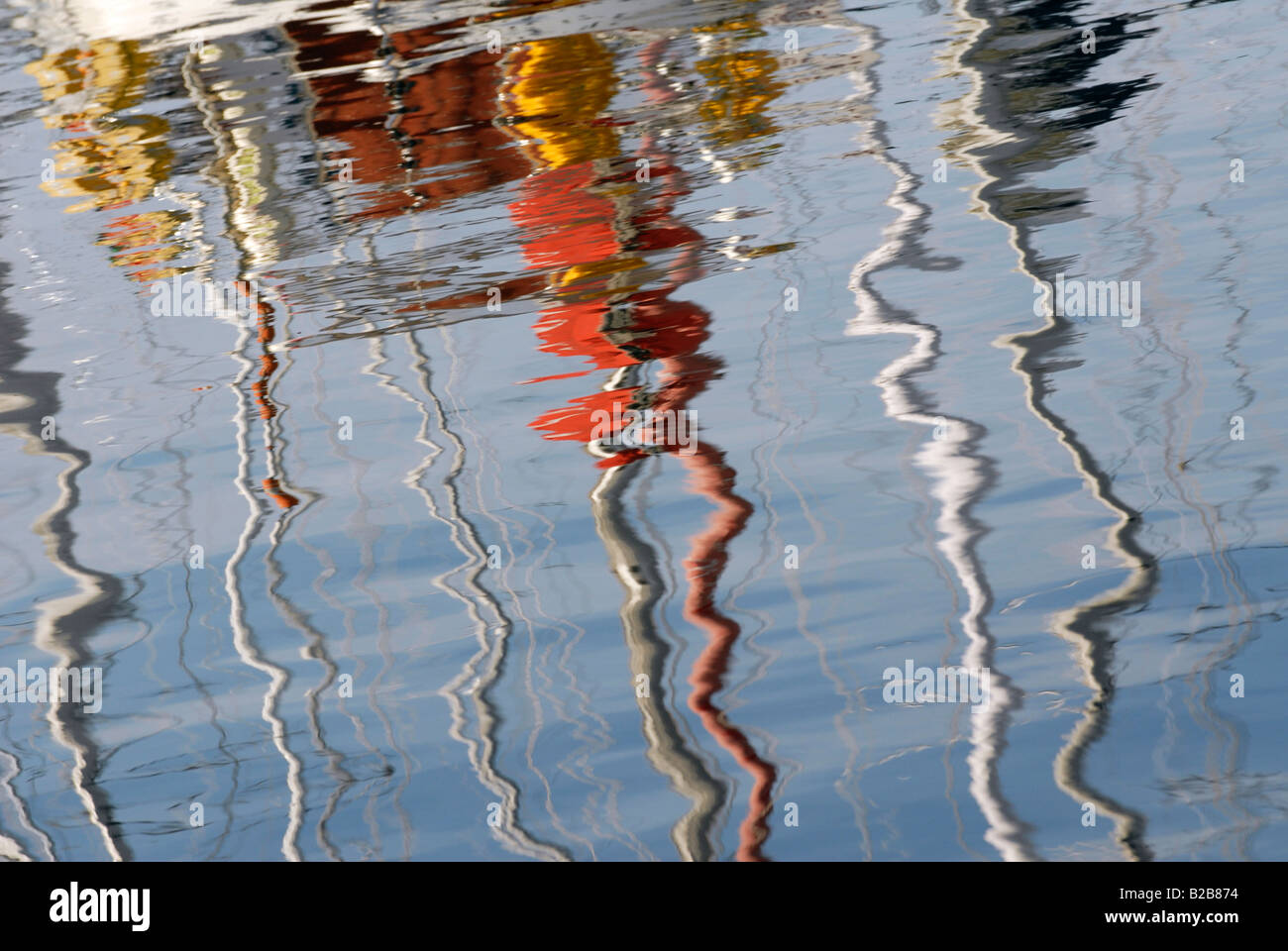 Sailing yacht masts reflected in rippling water - Stock Image