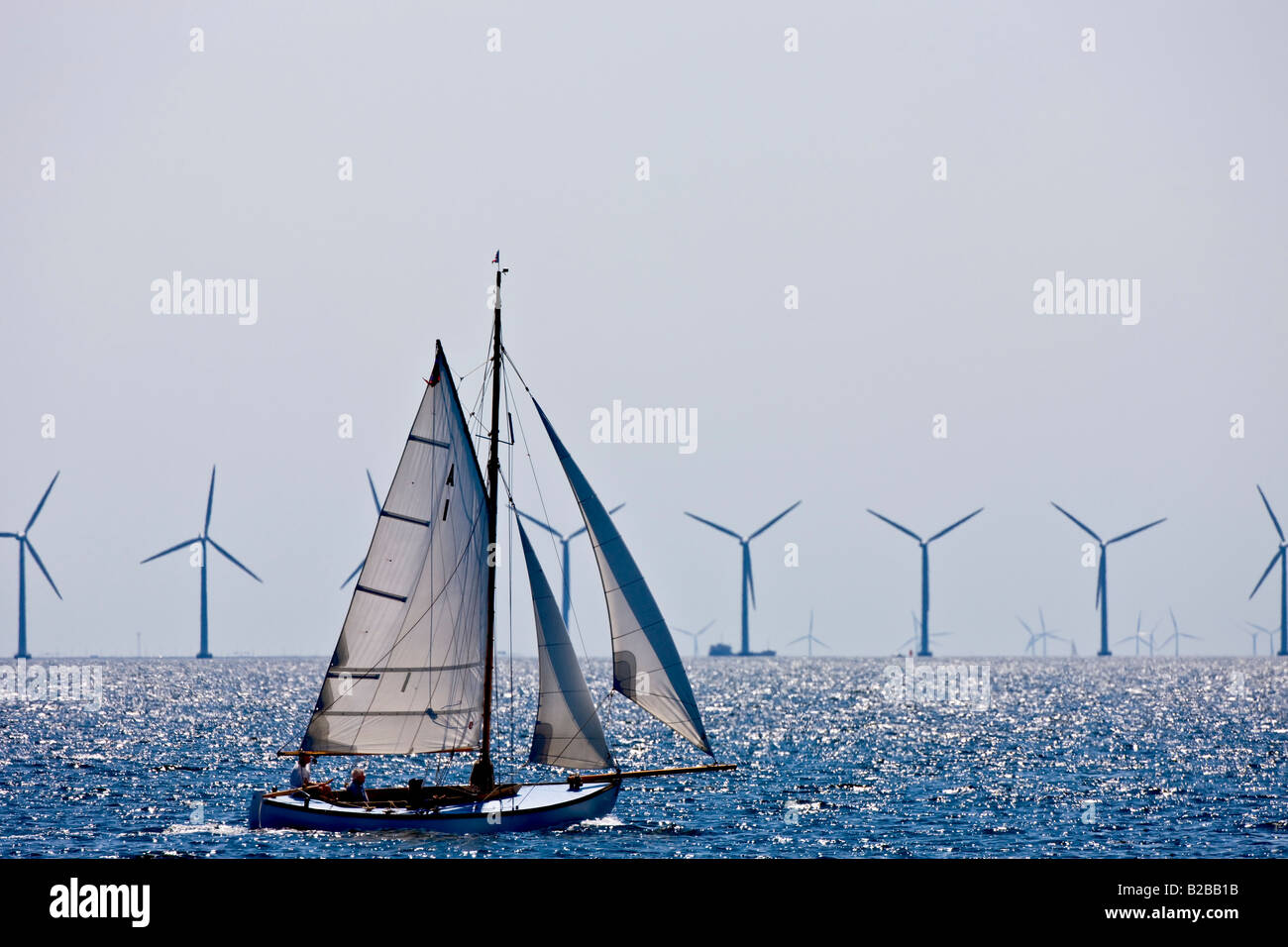 Sailing boat in front of an off shore wind park in the Sound between Denmark and Sweden - Stock Image