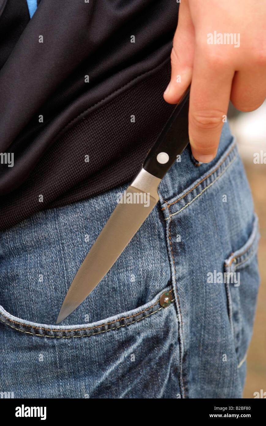 Knife crime boys hand holding a kitchen knife - Stock Image