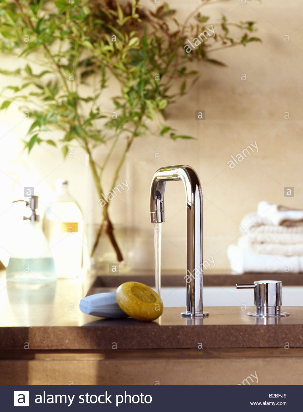 Soap next to running faucet - Stock Image