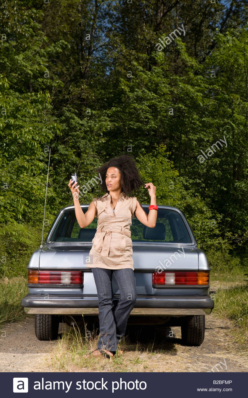 Woman with cell phone leaning on car trunk - Stock Image