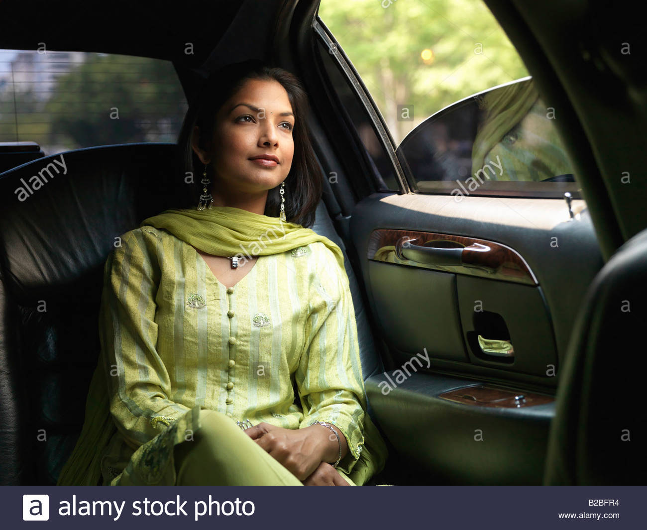 Indian woman in backseat of car - Stock Image