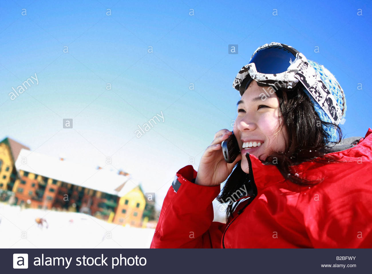 Asian skier talking on cell phone - Stock Image