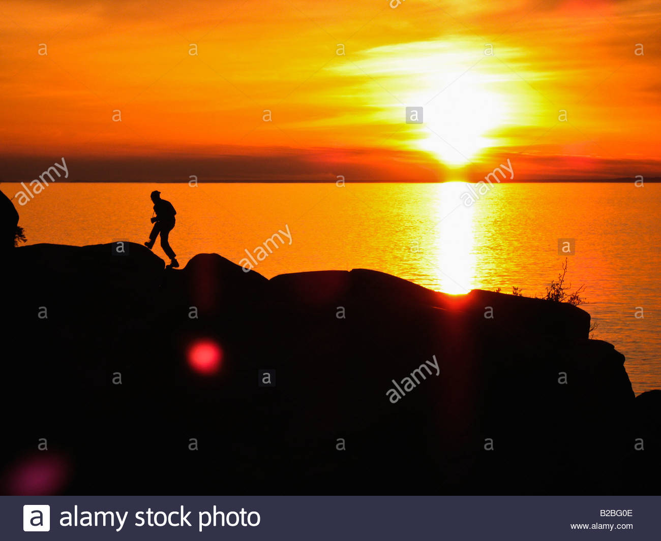 Person on cliff at sunset Stock Photo