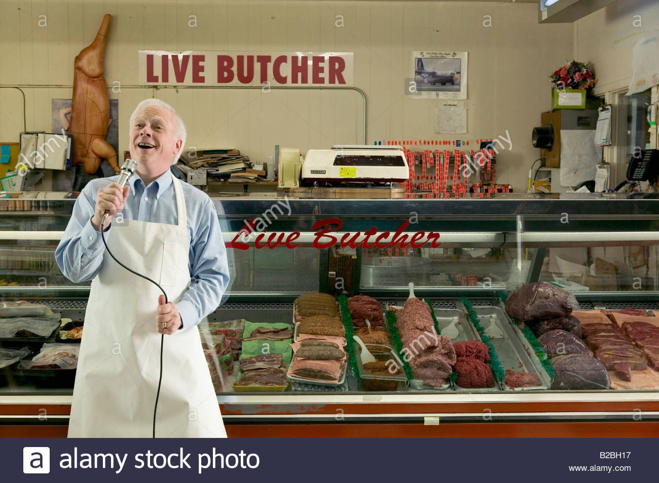 Butcher singing into microphone by meat counter - Stock Image