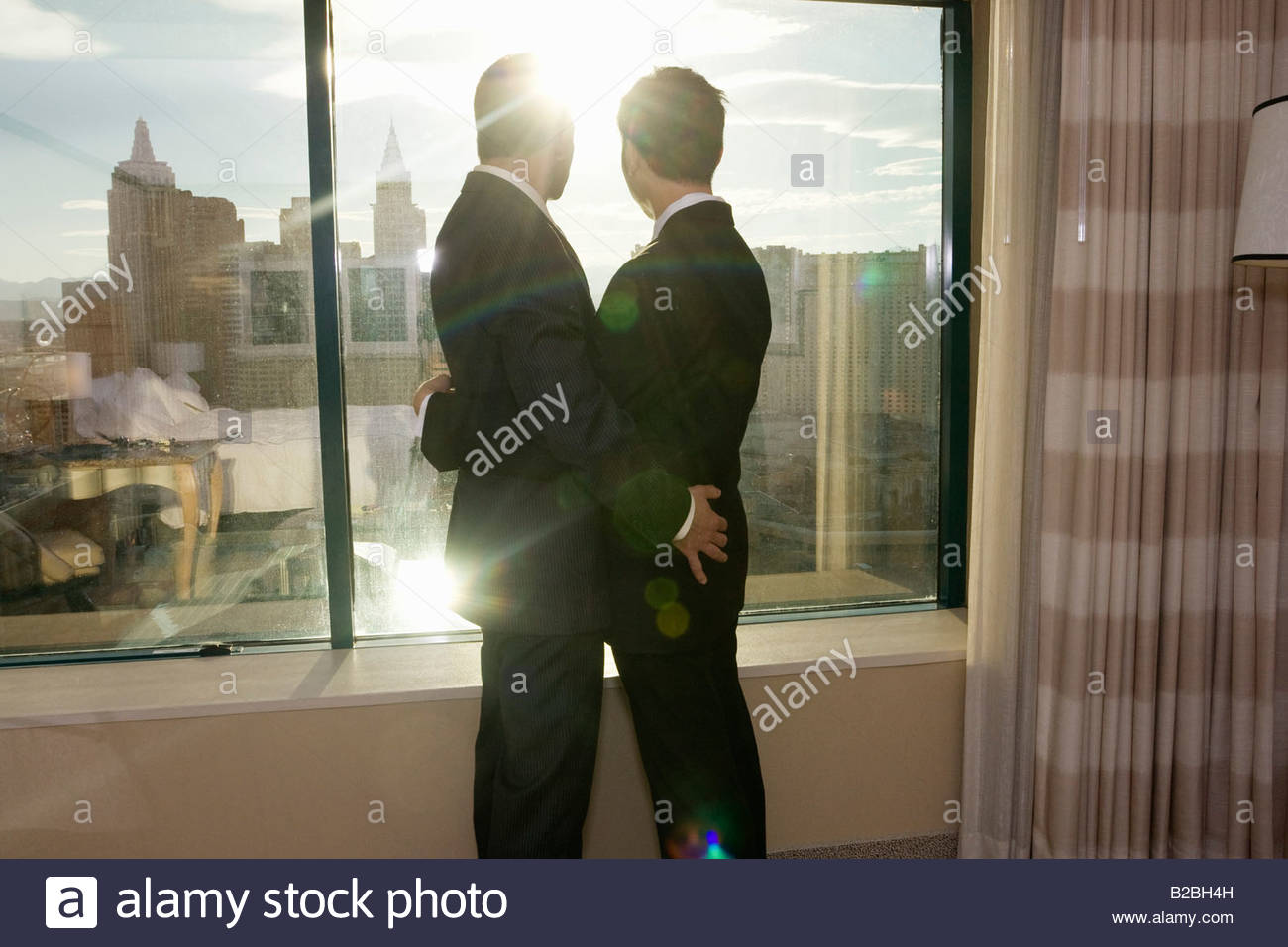 Businessmen hugging in hotel room - Stock Image
