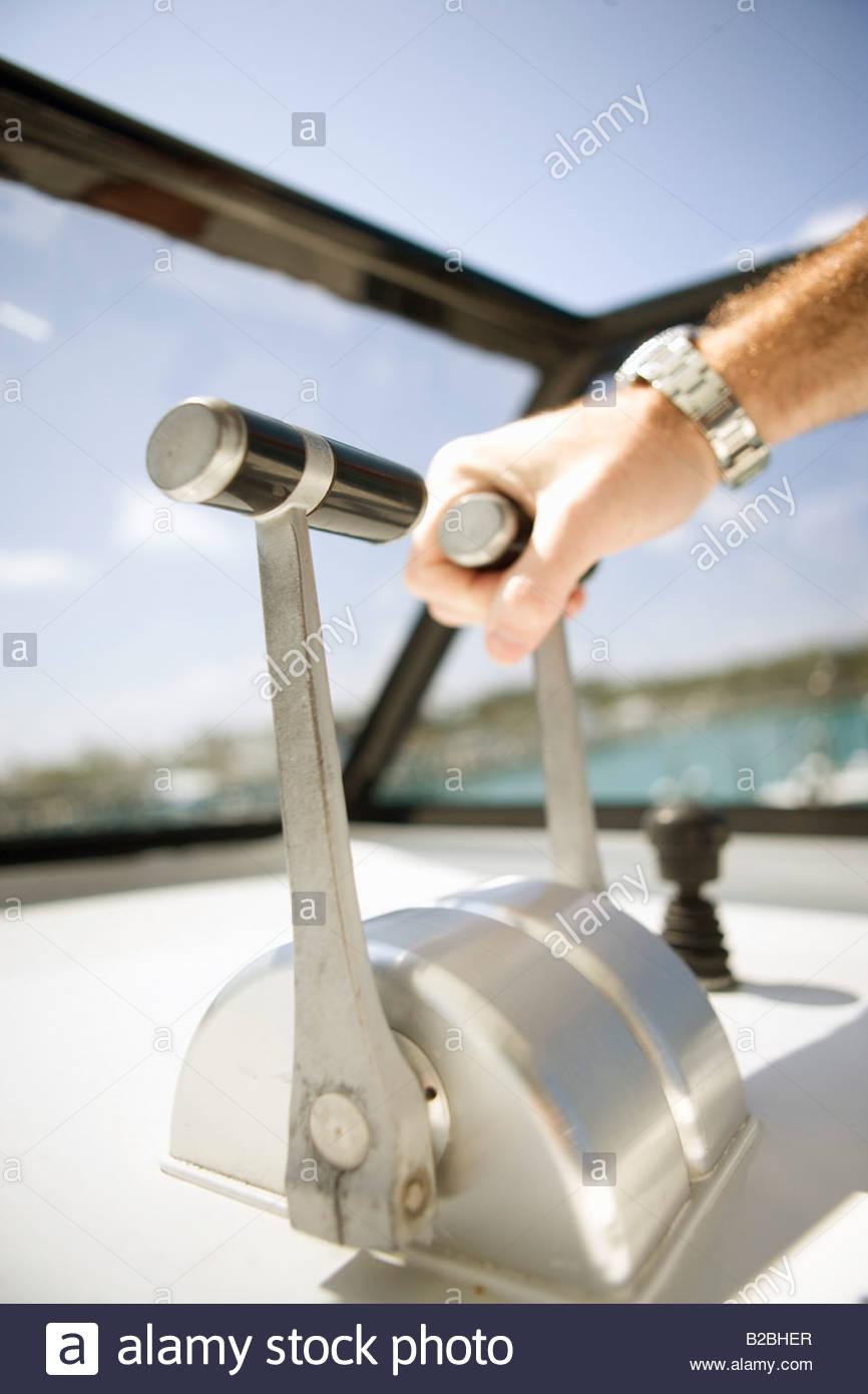 Man's hand on boat throttle - Stock Image