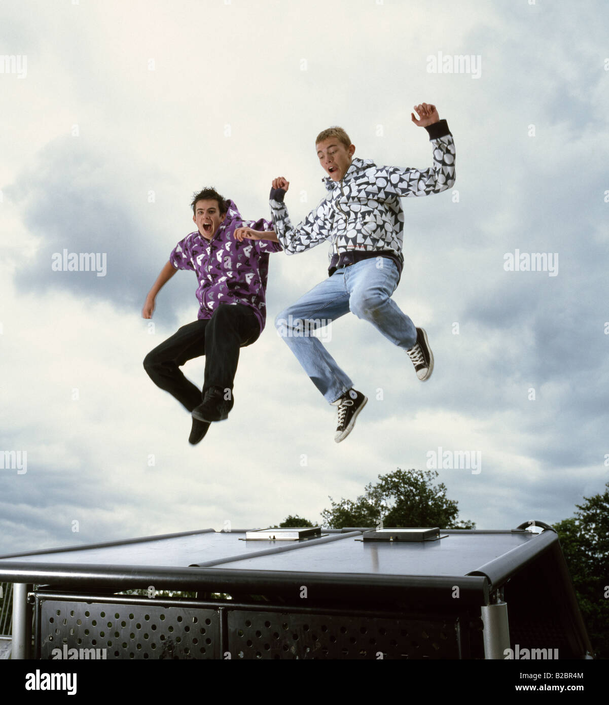 Two teenage boys jumping for joy. - Stock Image