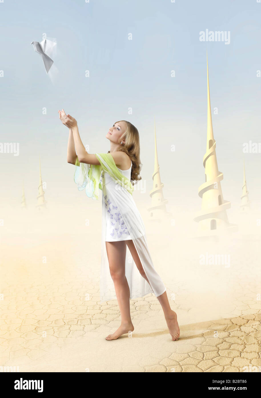 Young beautiful girl, releasing a white peace dove made of paper into the blue sky in an extraterrestrial desert - Stock Image