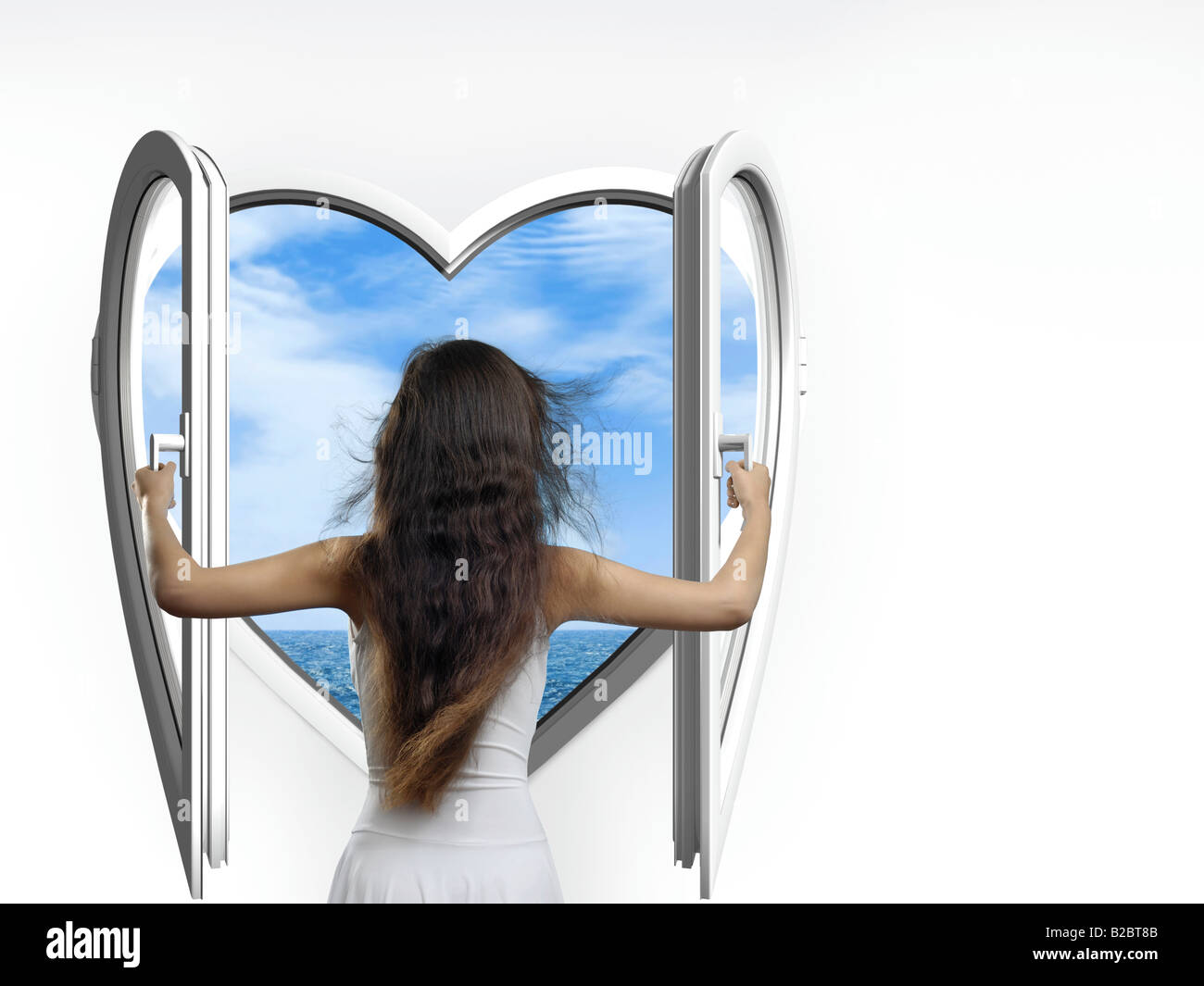 Beautiful woman wearing a white summer dress opening a heart-shaped window with a view of the sea, her long hair Stock Photo
