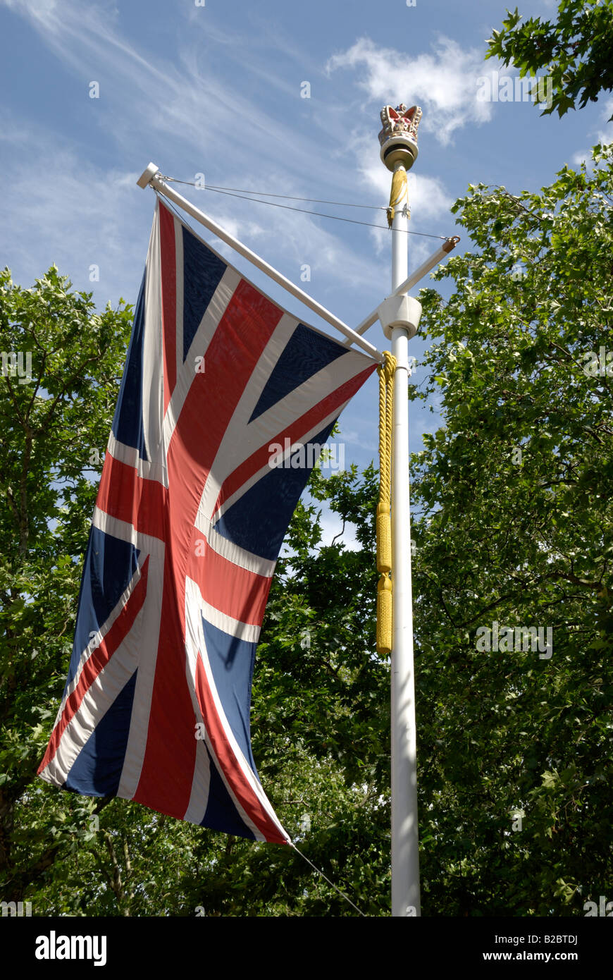 British flag on flagpole with trees in background, London - Stock Image