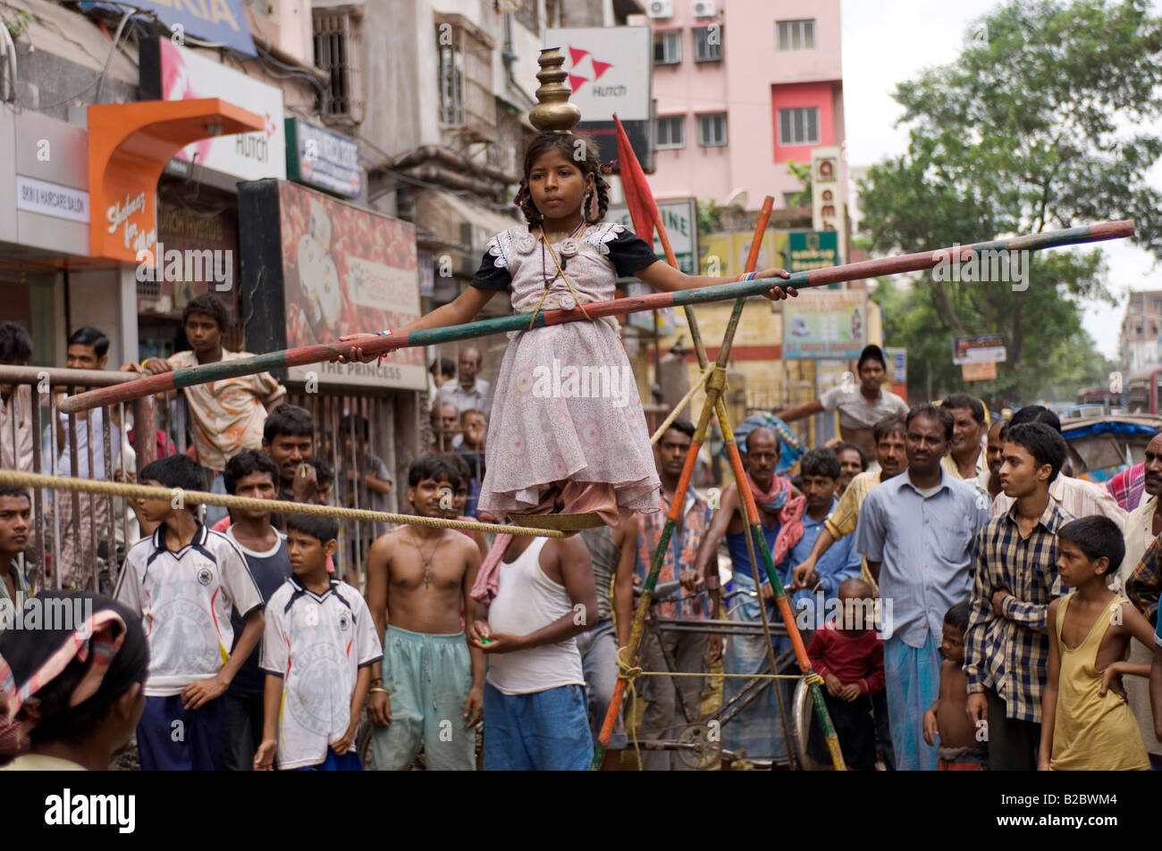 On a main street, a performing family earn their income. Howrah, Hooghly, West Bengal, India - Stock Image