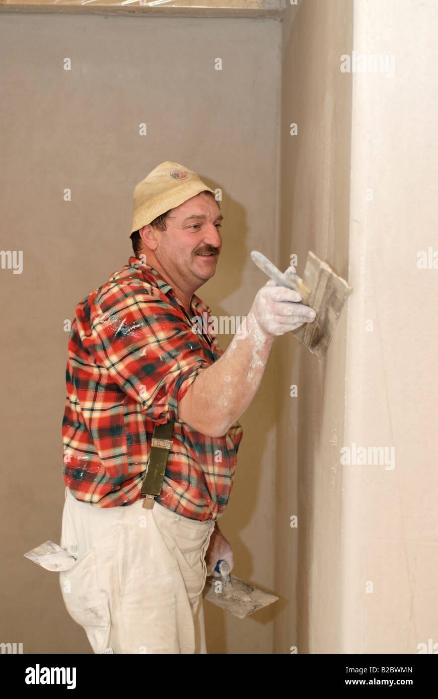 Plasterer at work, wave-like plaster, house construction, brickwork, interior works, plastering works - Stock Image