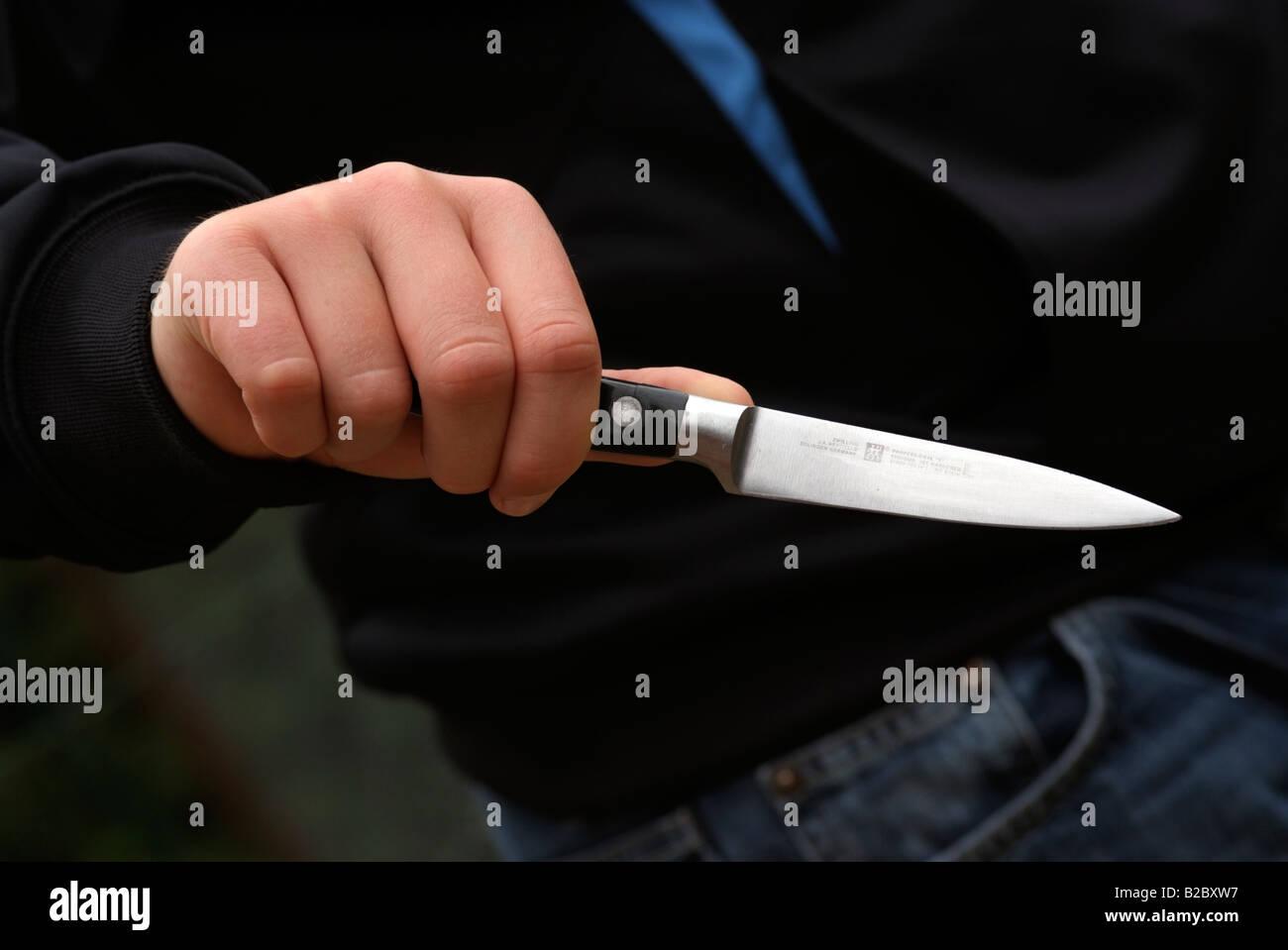 Knife crime. Boy's hand holding a kitchen knife - Stock Image
