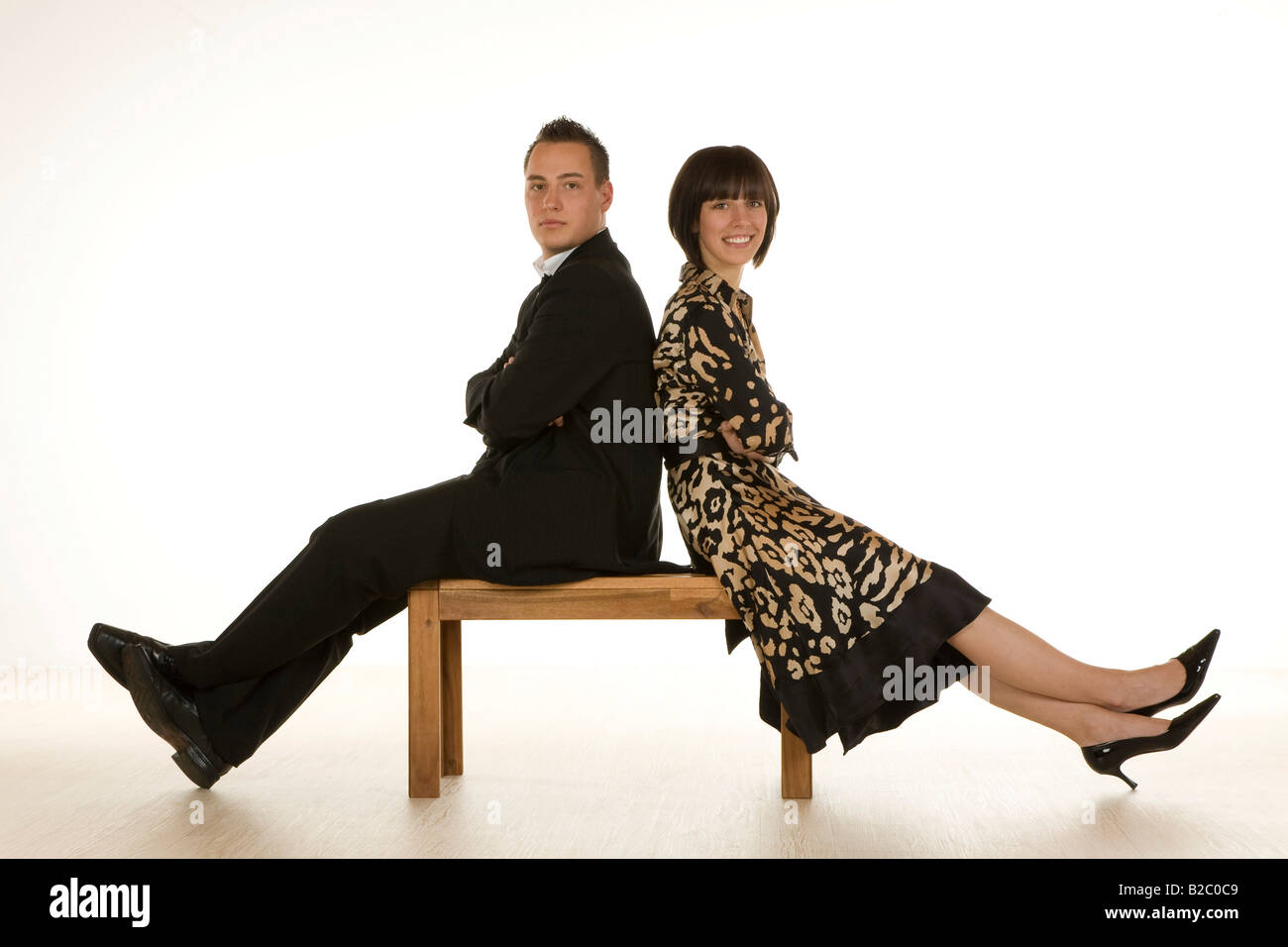 Man and woman in the early twenties sitting on a bench - Stock Image