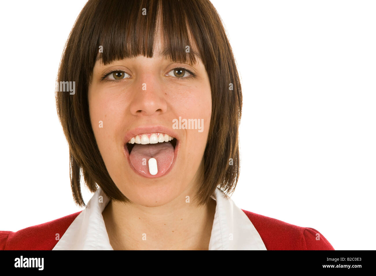 20-year-old woman with a tablet on her tounge Stock Photo