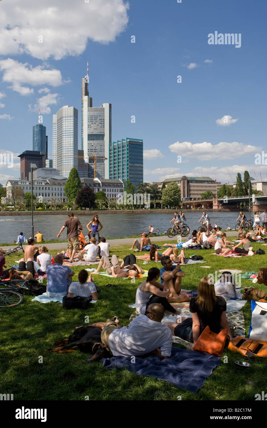 Bank of the River Main with people out in the sun, behind it the banking quarter with the Commerz Bank, Frankfurt, - Stock Image