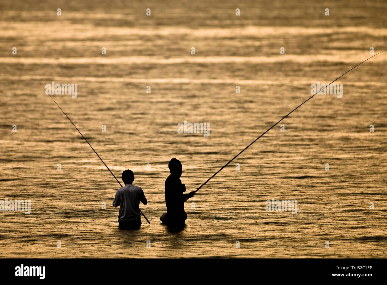 Two fishermen fishing at dusk, standing in the water under a gentle rain, Lombok Island, Indonesia, Asia - Stock Image