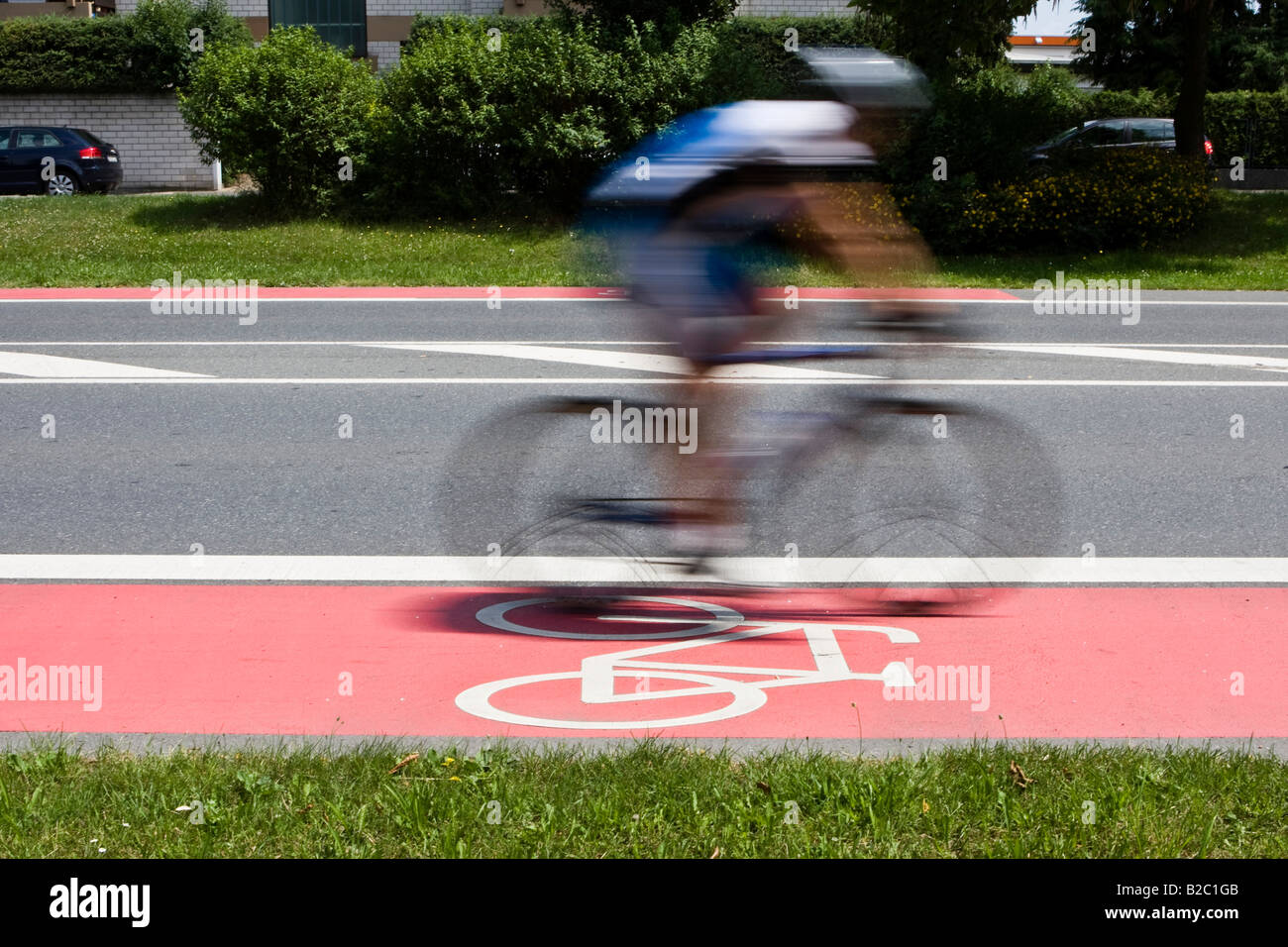 Cyclist riding quickly along a red bike lane with a bike lane street marking, Germany, Europe - Stock Image