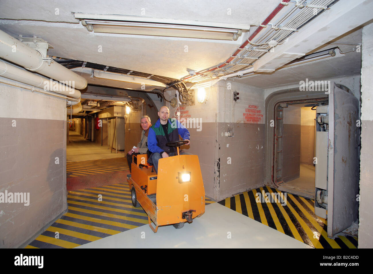 Employees driving an electric trolley through the corridors in the museum of the former Marienthal government bunker - Stock Image