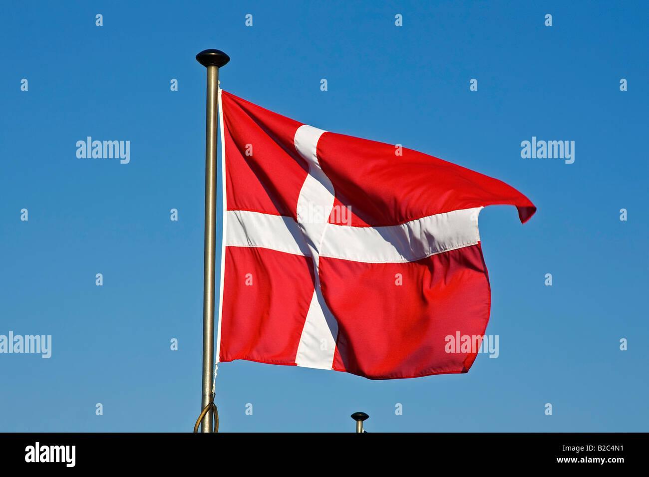 Danish Flag, Flag of Denmark, Dannebrog, fluttering in the wind on a flagpole - Stock Image