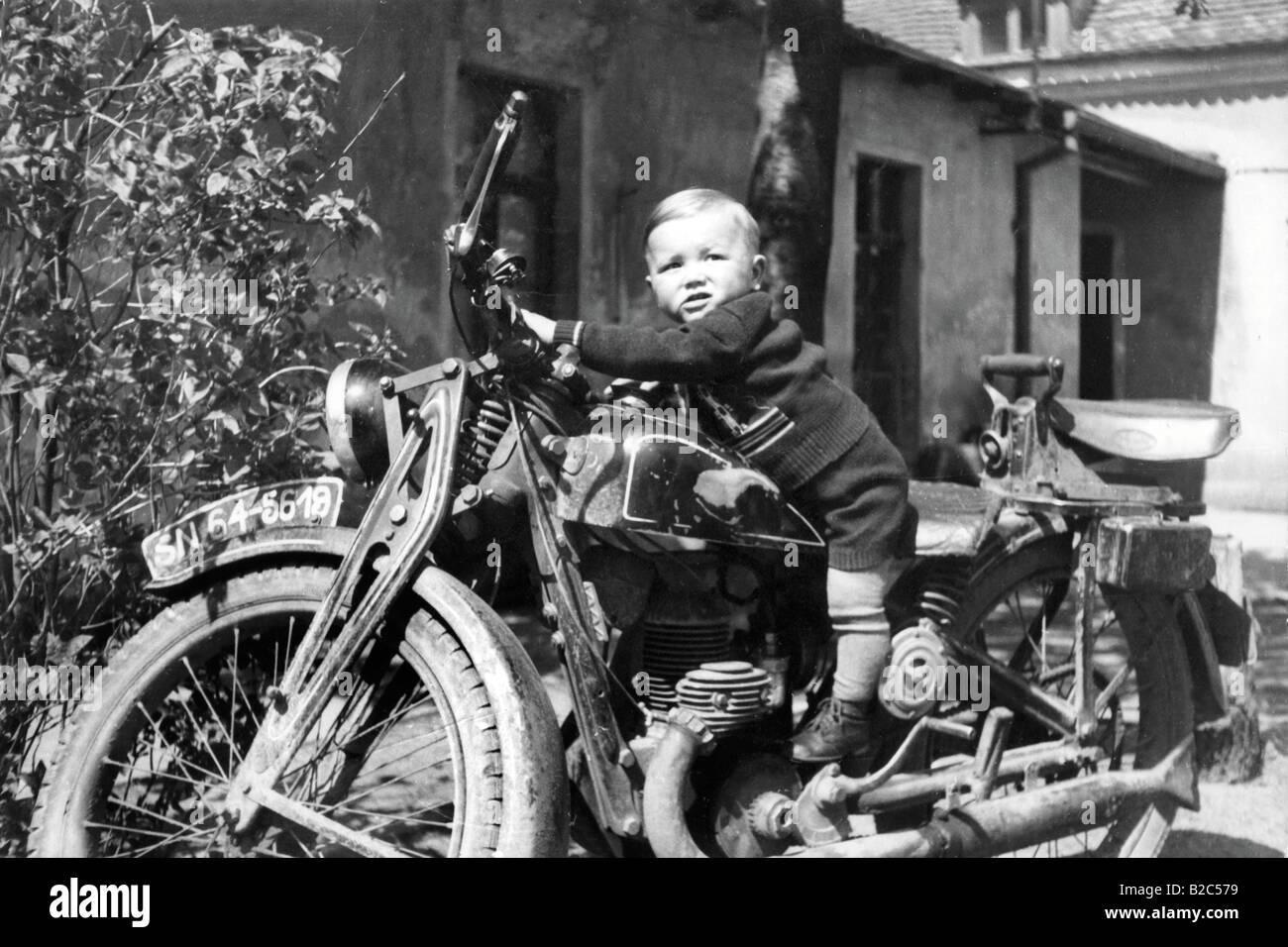 Small child on a motorbike, historical photo, circa 1940 - Stock Image
