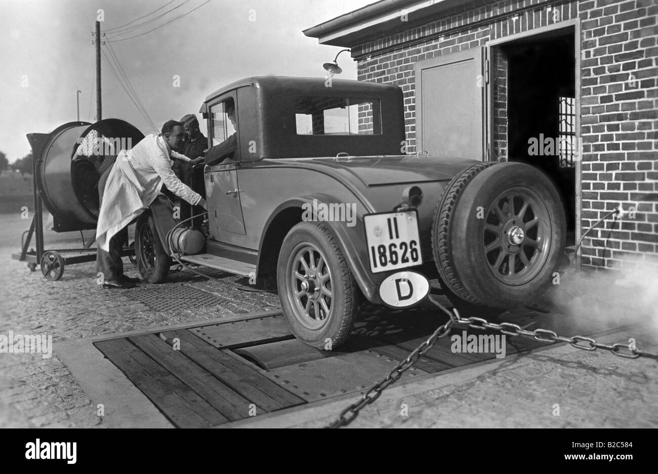 Car being checked, MOT, man looking at the car, historic picture from about 1930 - Stock Image