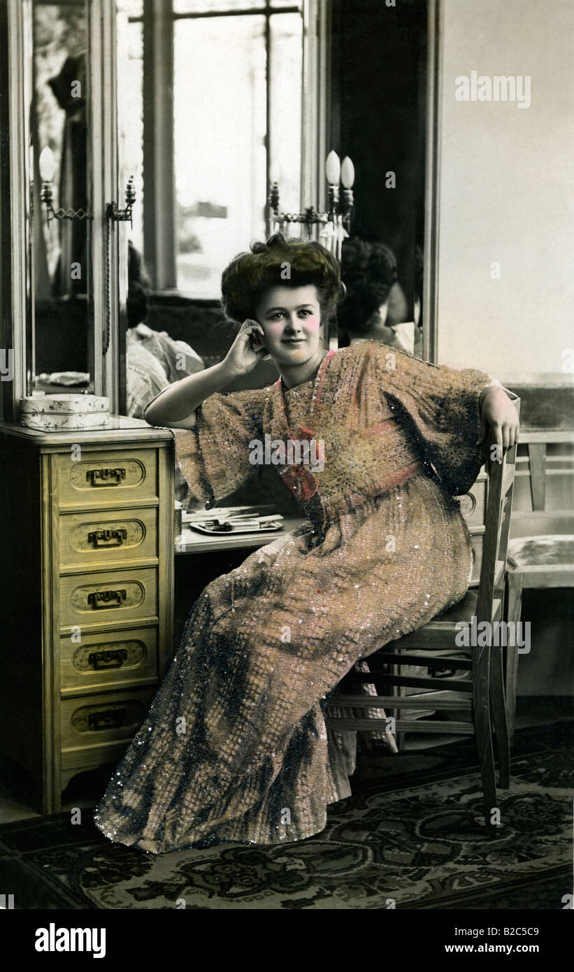 Woman in a dress posing in front of a mirror, historical photo, circa 1910 - Stock Image