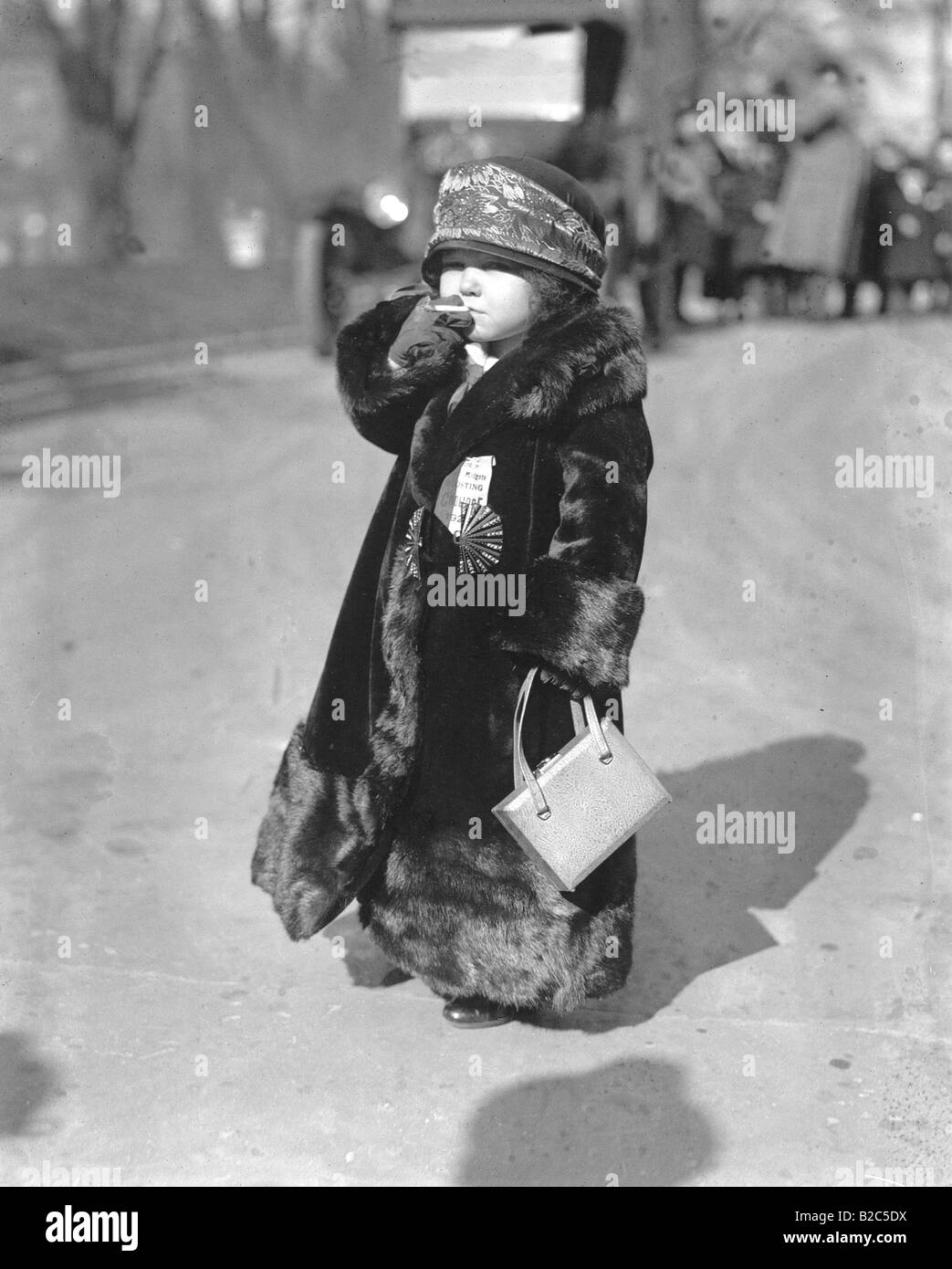 Child wearing a fur coat, smoking a cigarette, historic picture from about 1920 - Stock Image