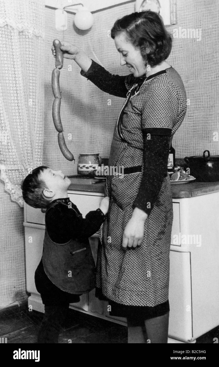 Mother teases boy with sausages, historical photo, circa 1940 - Stock Image