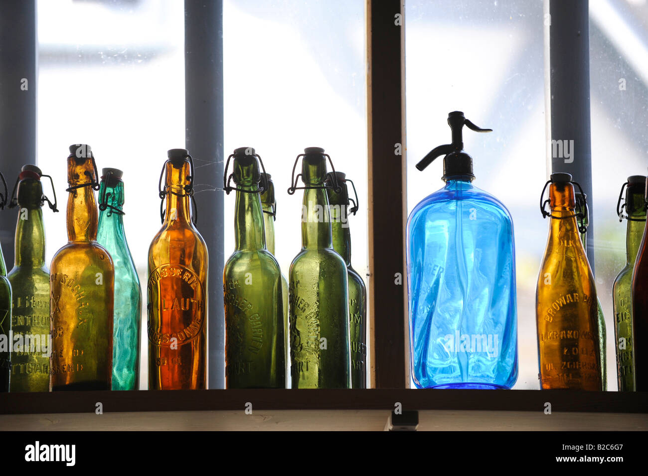 Colourful glass bottles in front of a window Stock Photo