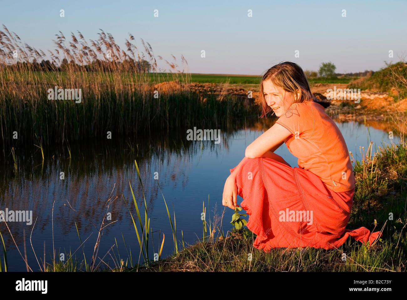 Girl dreamily kneeling next to a small lake in the evening sun - Stock Image