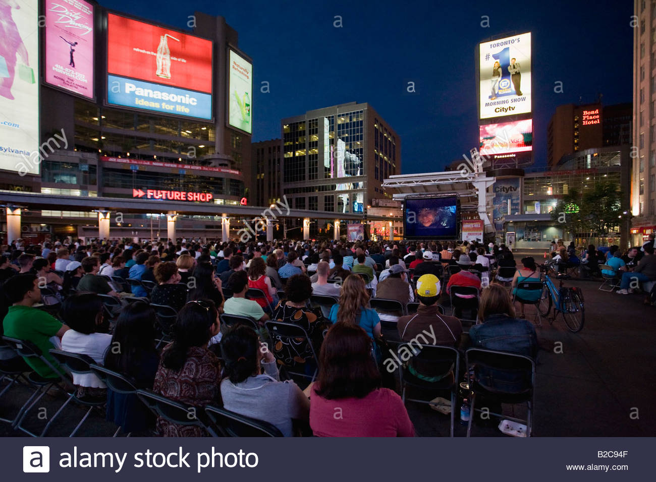 Crowds for outdoor movie night in Younge Dundas Square a public space on a summer night in Toronto Ontario Canada - Stock Image