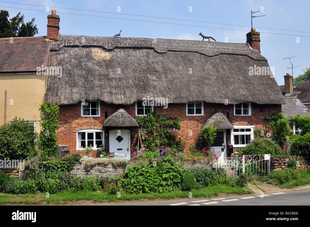 Thatched house at Cropredy, Oxfordshire with fox and peacock figures on top of the roof. - Stock Image