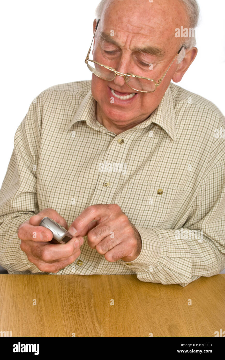 Vertical portrait of an elderly gentleman getting frustrated using the small buttons on a mobile phone - Stock Image