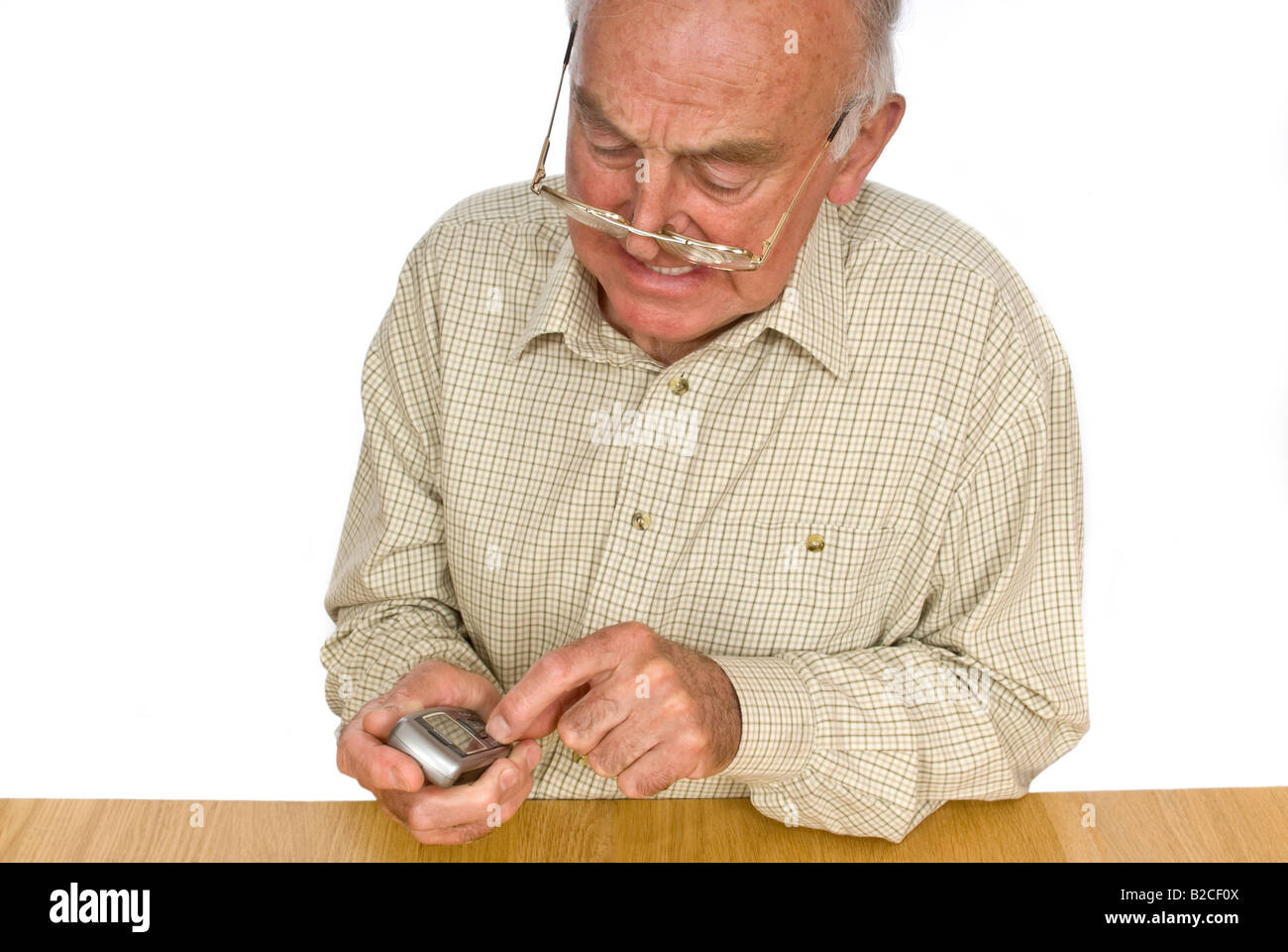 Horizontal portrait of an elderly gentleman getting frustrated using the small buttons on a mobile phone - Stock Image