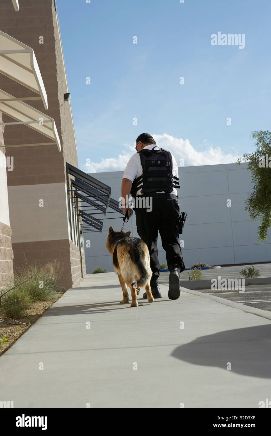 Security guard with dog on patrol - Stock Image