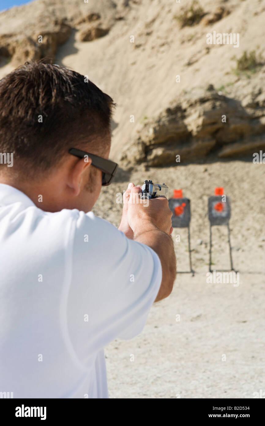 Man aiming hand gun at firing range - Stock Image