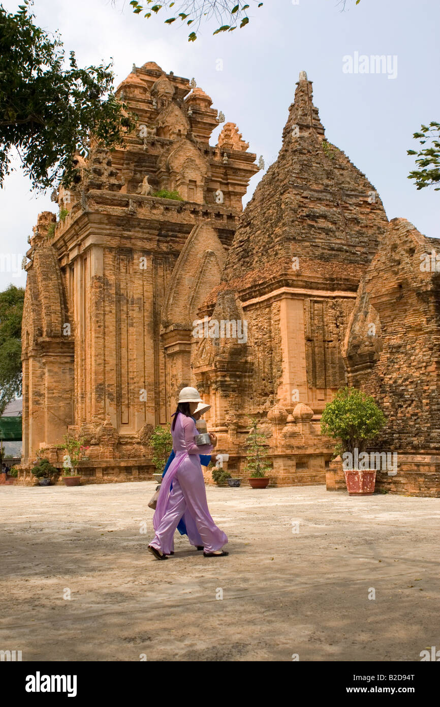 Women walk in front of the Po Nagar Tower at Nha Trang in Vietnam. The Po Nagar Towers are ancient temples. - Stock Image